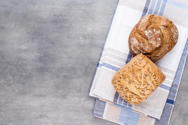 Pagnotte di pane e focacce croccanti rustiche oro su superficie di legno. natura morta catturata dall'alto vista dall'alto, piatto laici.