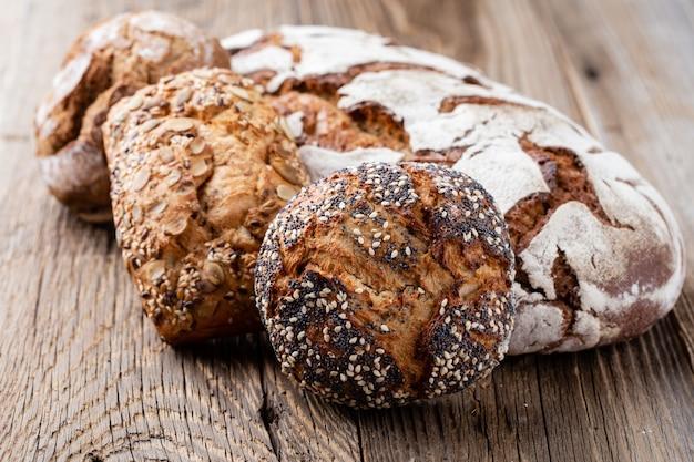 Pagnotte di pane e focacce croccanti rustiche dell'oro su legno.