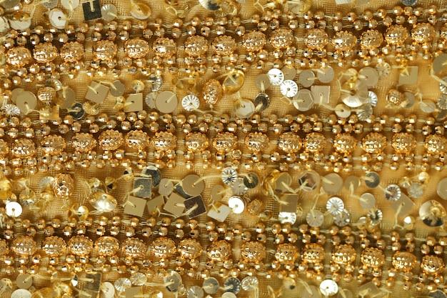 Sfondo di paillettes e perline d'oro. tessuto scintillante dai toni dorati. la trama del tessuto con paillettes e trombe.