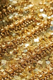 Sfondo di paillettes e perline d'oro. la trama del tessuto con paillettes e trombe.