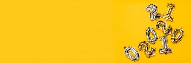 Numeri di aria oro e argento palloncini su uno sfondo giallo. composizione festiva, vista dall'alto.