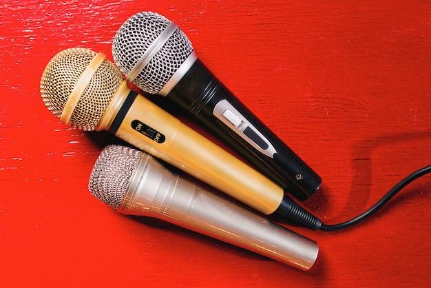Microfoni oro argento e bronzo su sfondo di legno rosso