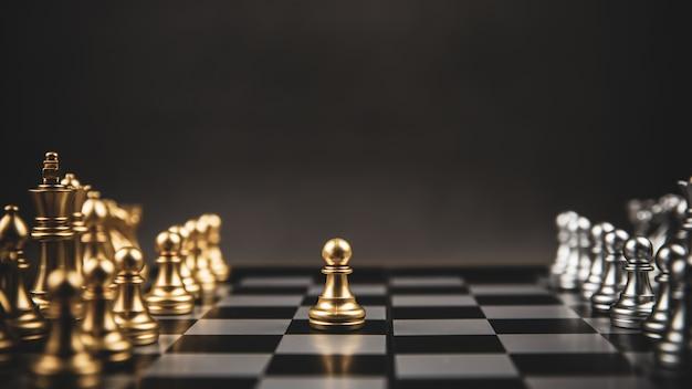 Oro e argento sfida squadra di scacchi sulla scacchiera concetto di piano strategico aziendale.