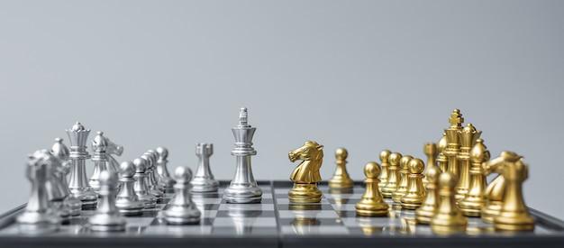 Figura di scacchi in oro e argento su scacchiera