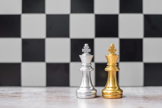 Figura del re degli scacchi in oro e argento sulla scacchiera contro avversario o nemico. strategia, conflitto, gestione, pianificazione aziendale, tattica, politica, comunicazione e concetto di leader