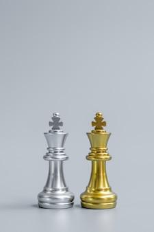 Figura del re degli scacchi in oro e argento sulla scacchiera contro avversario o nemico.