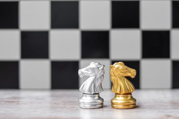 Figura di cavaliere degli scacchi in oro e argento con sfondo di manager di uomo d'affari.