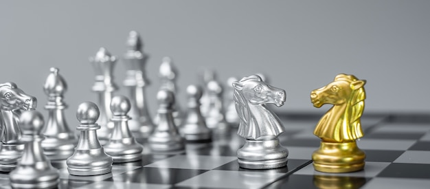 Figura d'oro e d'argento del cavaliere degli scacchi (cavallo) sulla scacchiera contro avversario o nemico.
