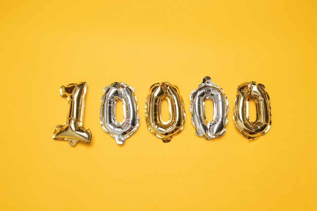 Oro e silvr 10.000 palloncini numerati su sfondo giallo. seguaci e concetto di abbonamento