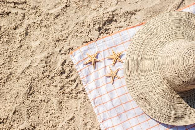 Stella marina d'oro, cappello sulla spiaggia sabbiosa. vista dall'alto, piatto.