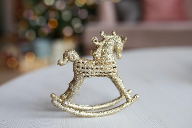 Cavallo di arredamento giocattolo d'oro in piedi sul tavolo contro lo sfondo di un albero bokeh e ghirlande