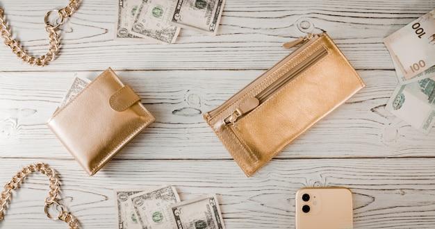 Portafogli d'oro, una catena d'oro, dollari, rubli, uno smartphone costoso su uno sfondo di legno