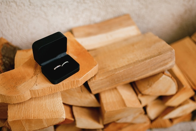Fedi nuziali in oro in una scatola di velluto nero su legno tagliato