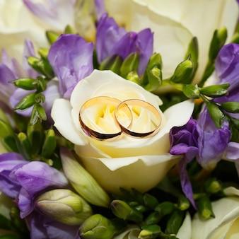 Fedi nuziali d'oro su un mazzo di fiori per la sposa