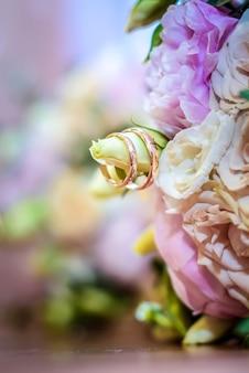 Anelli di nozze d'oro su un ramo di delicato bouquet di rose e peonie