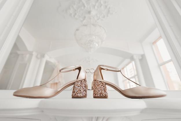 Fedi nuziali in oro tra le scarpe da sposa della sposa