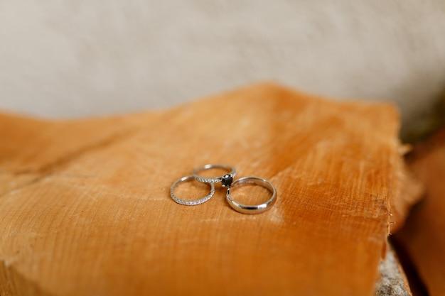 Fedi nuziali in oro e anello di fidanzamento su sfondo sfocato di struttura in legno liscio