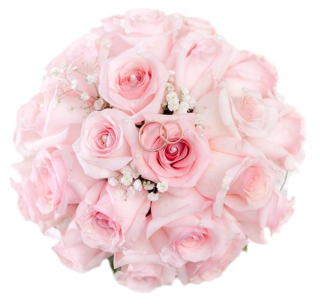 Fedi nuziali d'oro dello sposo e della sposa su un mazzo di fiori. isolato