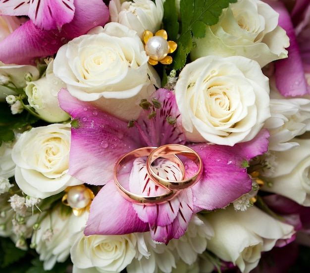 Fedi nuziali d'oro dello sposo e della sposa su un mazzo di fiori.