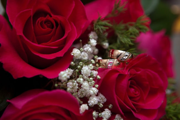 Le fedi nuziali d'oro dello sposo e della sposa giacciono su un bouquet della sposa