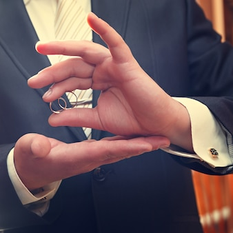 Fedi nuziali d'oro su una mano dello sposo