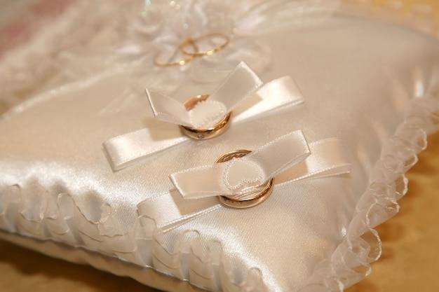 Gli anelli di nozze d'oro giacciono su un cuscino decorativo. amore e relazioni familiari