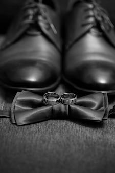 Le fedi nuziali d'oro giacciono sul tavolo accanto al papillon e alle scarpe da uomo