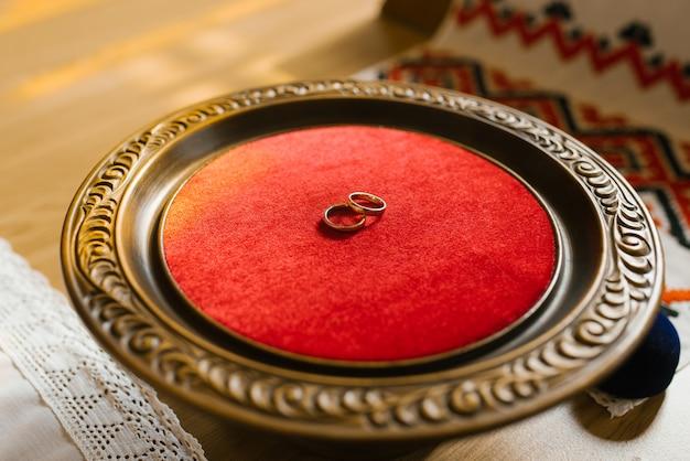 Le fedi nuziali dell'oro si trovano su un piatto di legno con velluto rosso