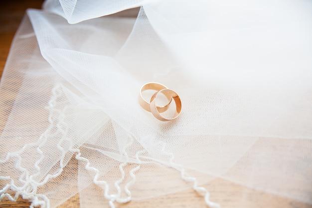 Anelli di nozze d'oro su un velo bianco