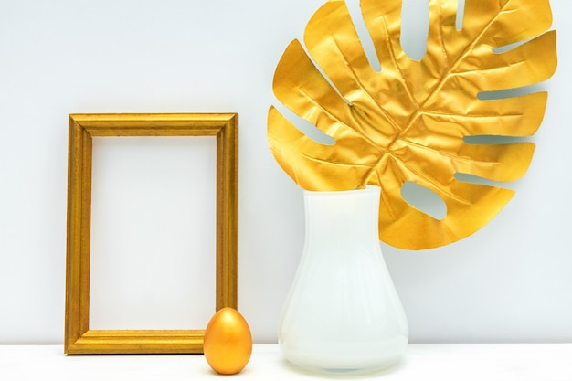 Interni oro e bianchi. portafoto vuoto, uovo dipinto e foglia di monstera.