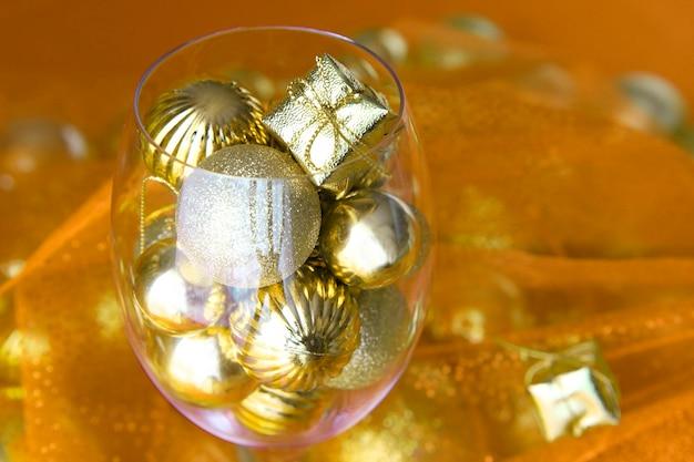 Sfondo di natale oro e giallo con decorazioni natalizie in vetro e oro al suo interno. bicchiere di vino con decorazioni natalizie