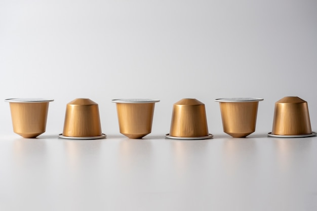 Le capsule di alluminio dorato con caffè macinato per la macchina da caffè sono visualizzate in fila su uno sfondo bianco