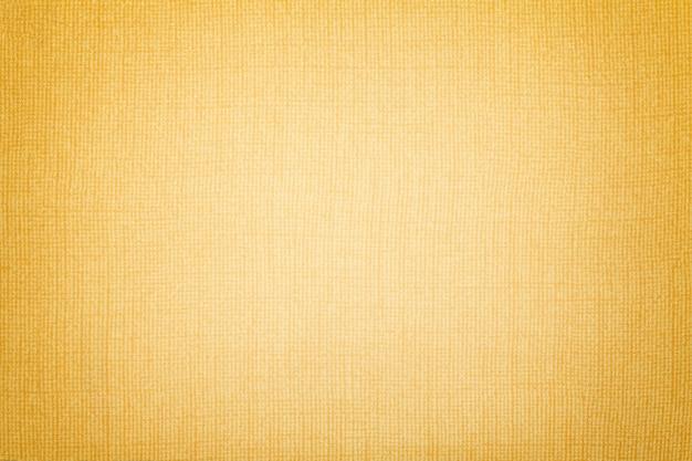 Sfondo dorato da materiale tessile. tessuto con trama naturale.