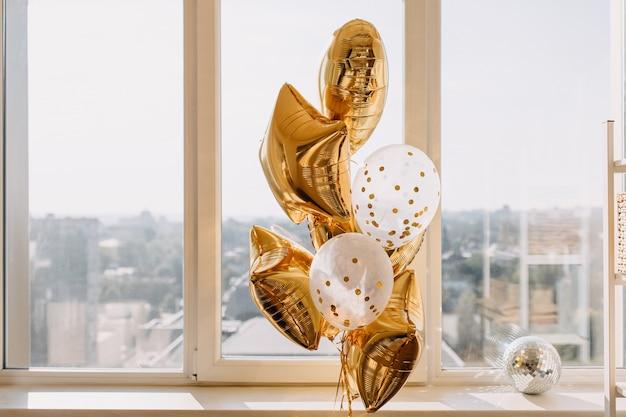 Palloncini dorati con elio nel soggiorno vicino alla finestra