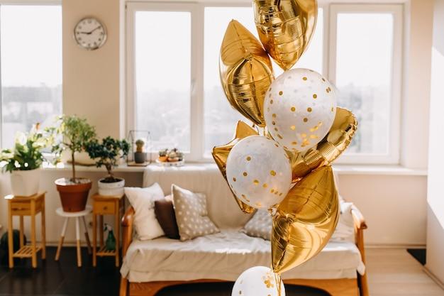 Palloncini dorati con elio in soggiorno per una festa a sorpresa