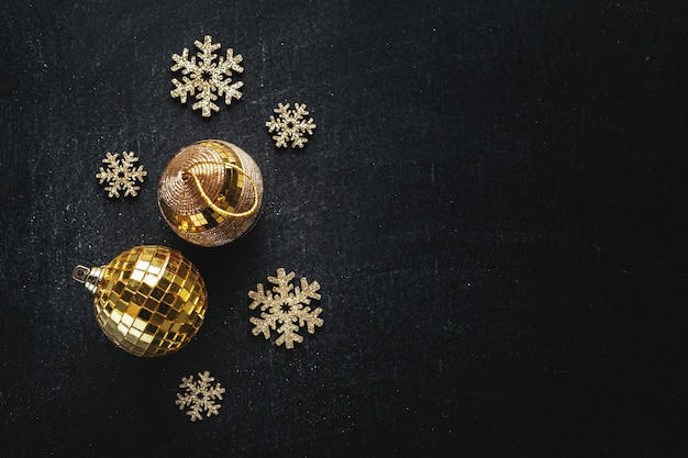 Bagattelle dorate con fiocchi di neve dorati sul nero. lay piatto.
