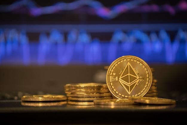 I bitcoin dorati sono impilati su uno sfondo luminoso di grafici commerciali in primo piano