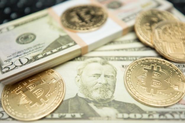 Moneta bitcoin dorata su dollari americani da vicino. immagine simbolica della valuta virtuale.