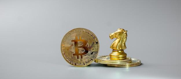 Pila di monete d'oro di criptovaluta bitcoin e pezzo del cavaliere degli scacchi
