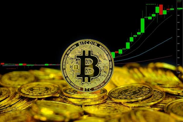 Criptovaluta bitcoin dorata sulla moneta d'oro dello stack sullo sfondo del grafico di trading