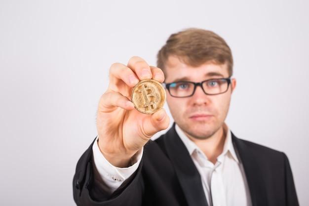 Bitcoin dorato in una mano dell'uomo, simbolo digitale di una criptovaluta virtuale.