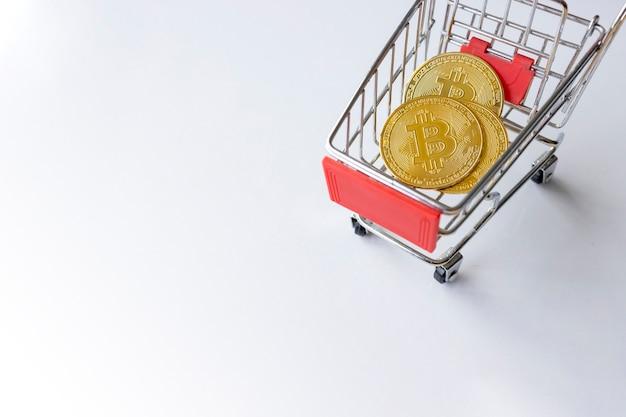 Bitcoin dorato nel carrello su sfondo bianco da tavola. vista dall'alto