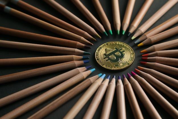 Valuta virtuale bitcoin dorato su sfondo nero con matite colorate