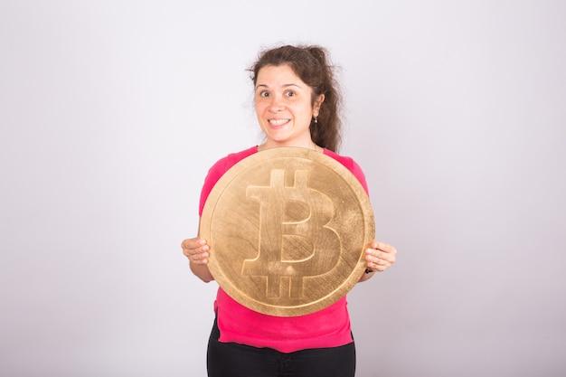 Bitcoin dorato in una mano di donna, simbolo digitale di una criptovaluta virtuale.
