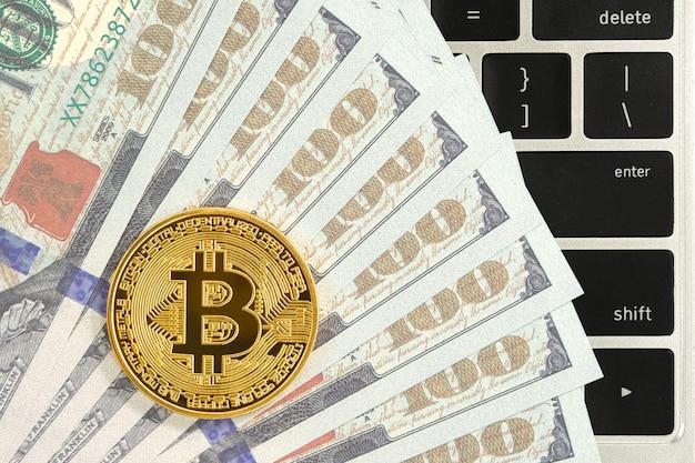 Moneta d'oro bitcoin e computer con tastiera di banconote degli stati uniti. close up di metallo lucido bitcoin crypto monete di valuta e dollaro usa