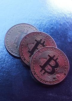 Bitcoin dorati isolati su sfondo blu ravvicinato con spazio di copia, concetto di crescita e caduta di criptovaluta