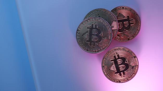 Bitcoin dorati isolati su sfondo viola rosa blu neon close-up con spazio copia, concetto di crescita e caduta di criptovaluta