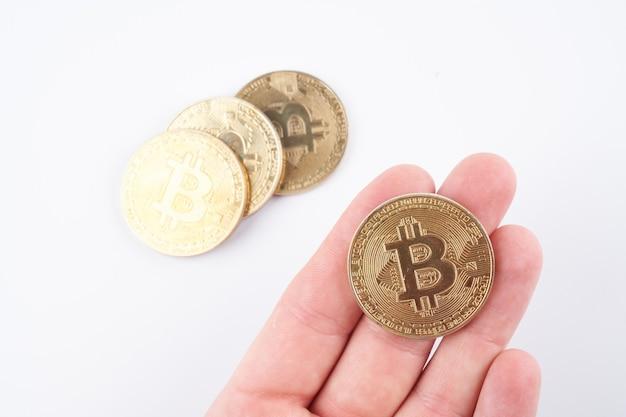 Bitcoin d'oro nel palmo della mano isolato su sfondo bianco ravvicinato con spazio di copia