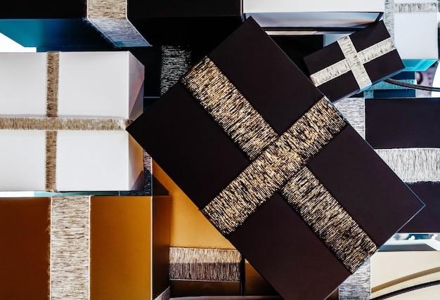 Scatole bianche nere dorate regali di natale con nastri. regali di capodanno