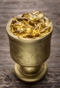 Ciotola d'oro con pillole dimagranti d'oro. vitamina e.